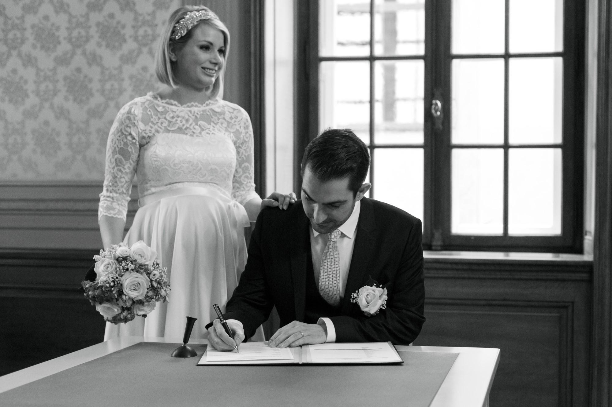 Bräutigam unterschreibt im Standesamt
