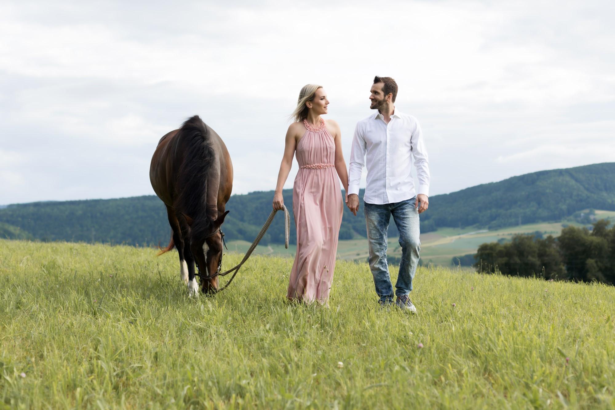Verliebtes Paar spaziert mit ihrem Pferd über Wiesen