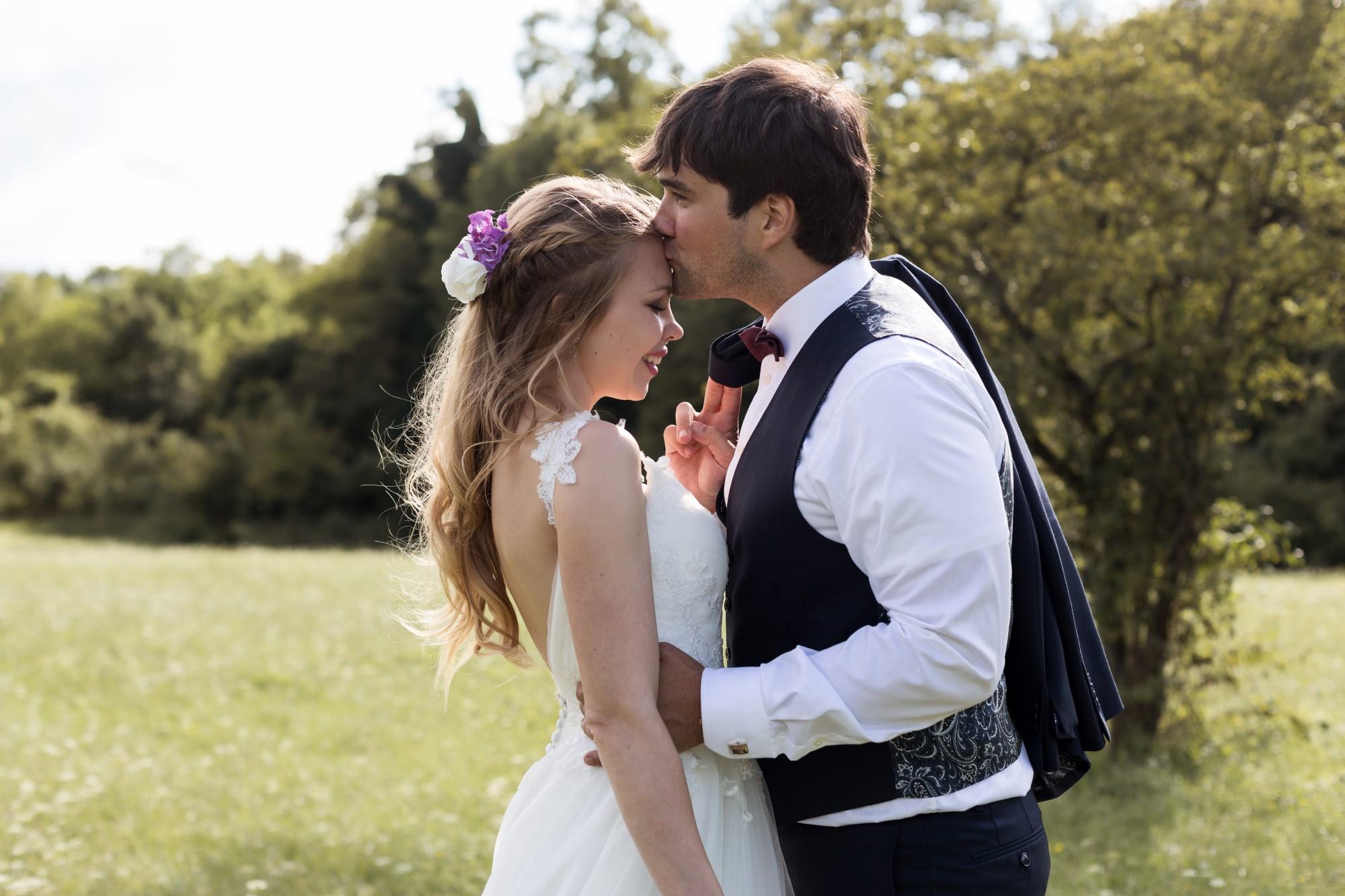 Der Bräutigam küsst die Braut auf die Stirn