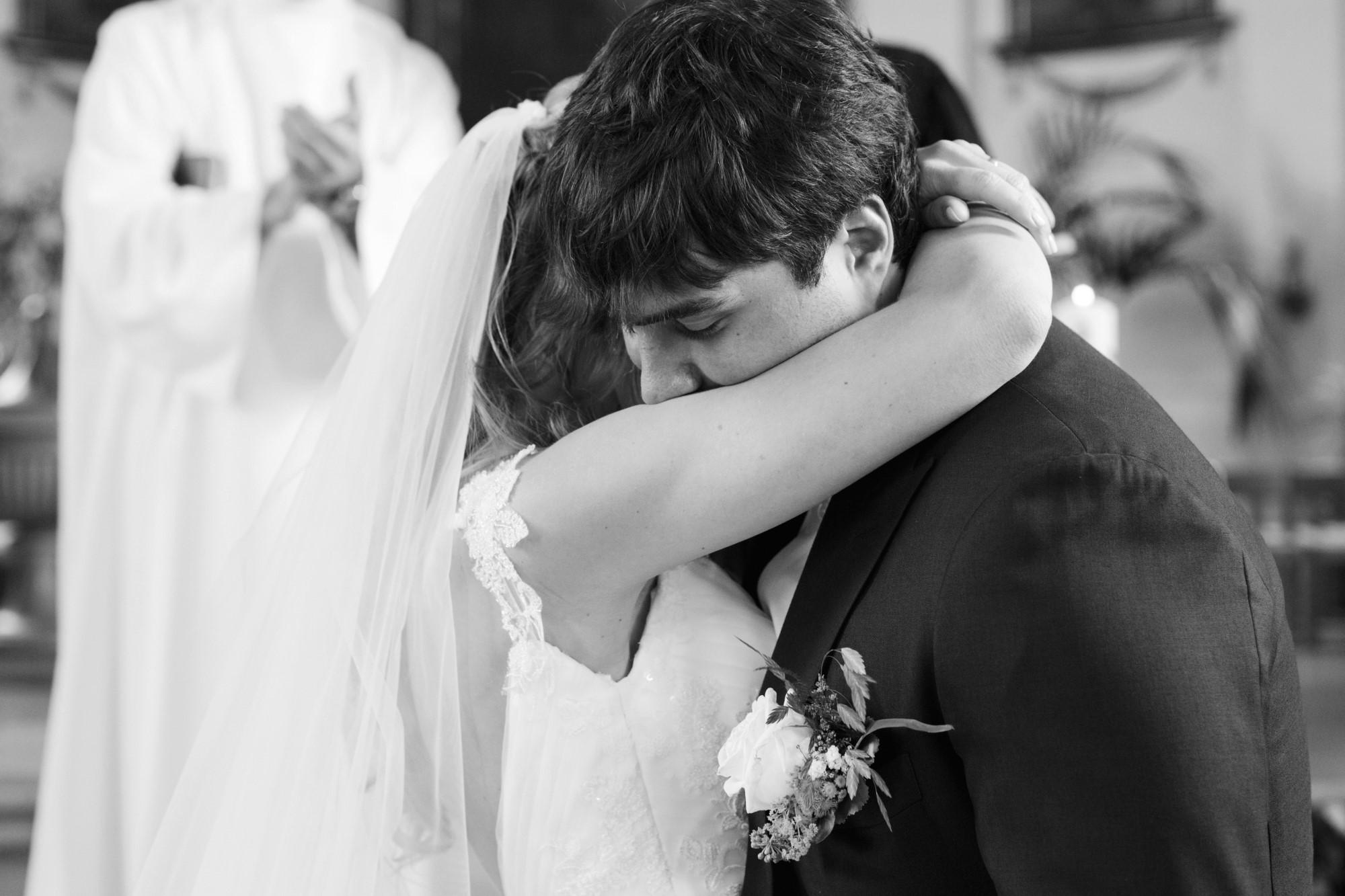 Inniger Moment in der Kirche - Das Brautpaar umarmt sich