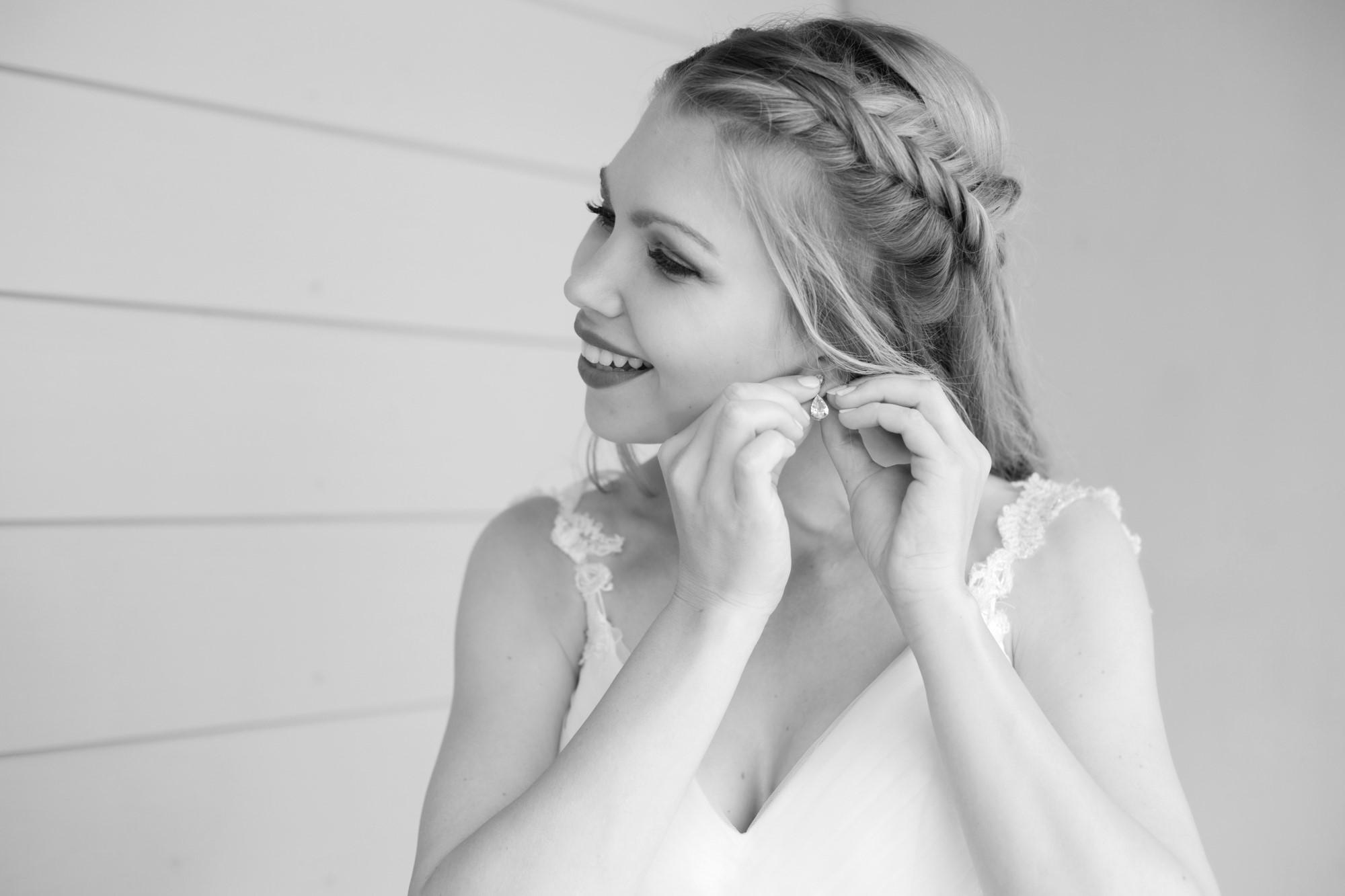 Braut steckt sich den Ohrring an - Getting Ready der Braut