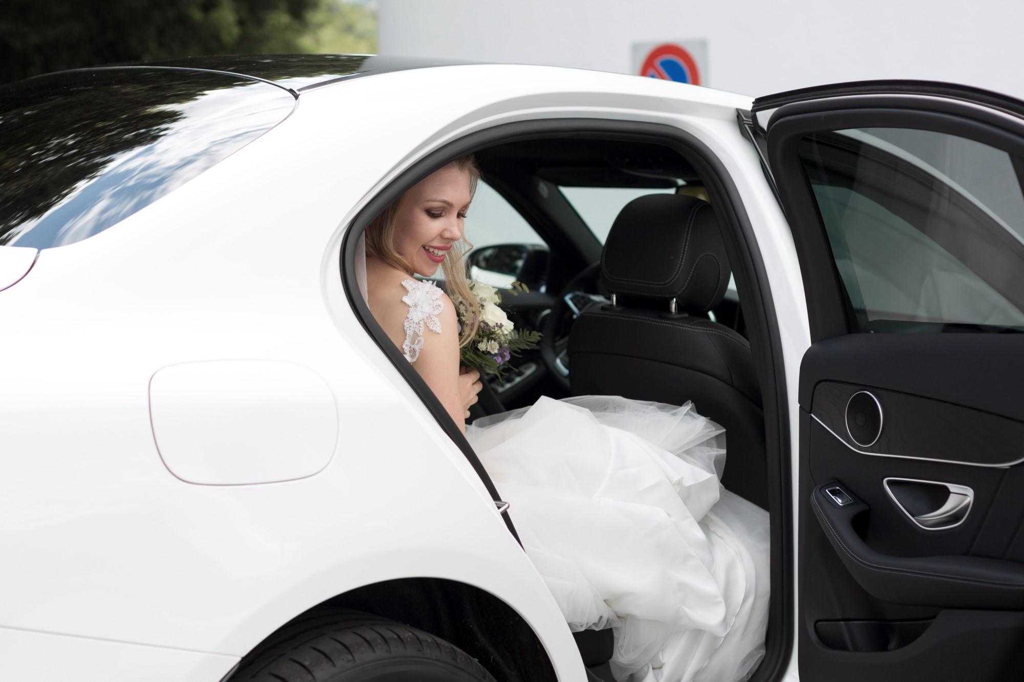 Die Braut steigt aus dem Hochzeitswagen aus