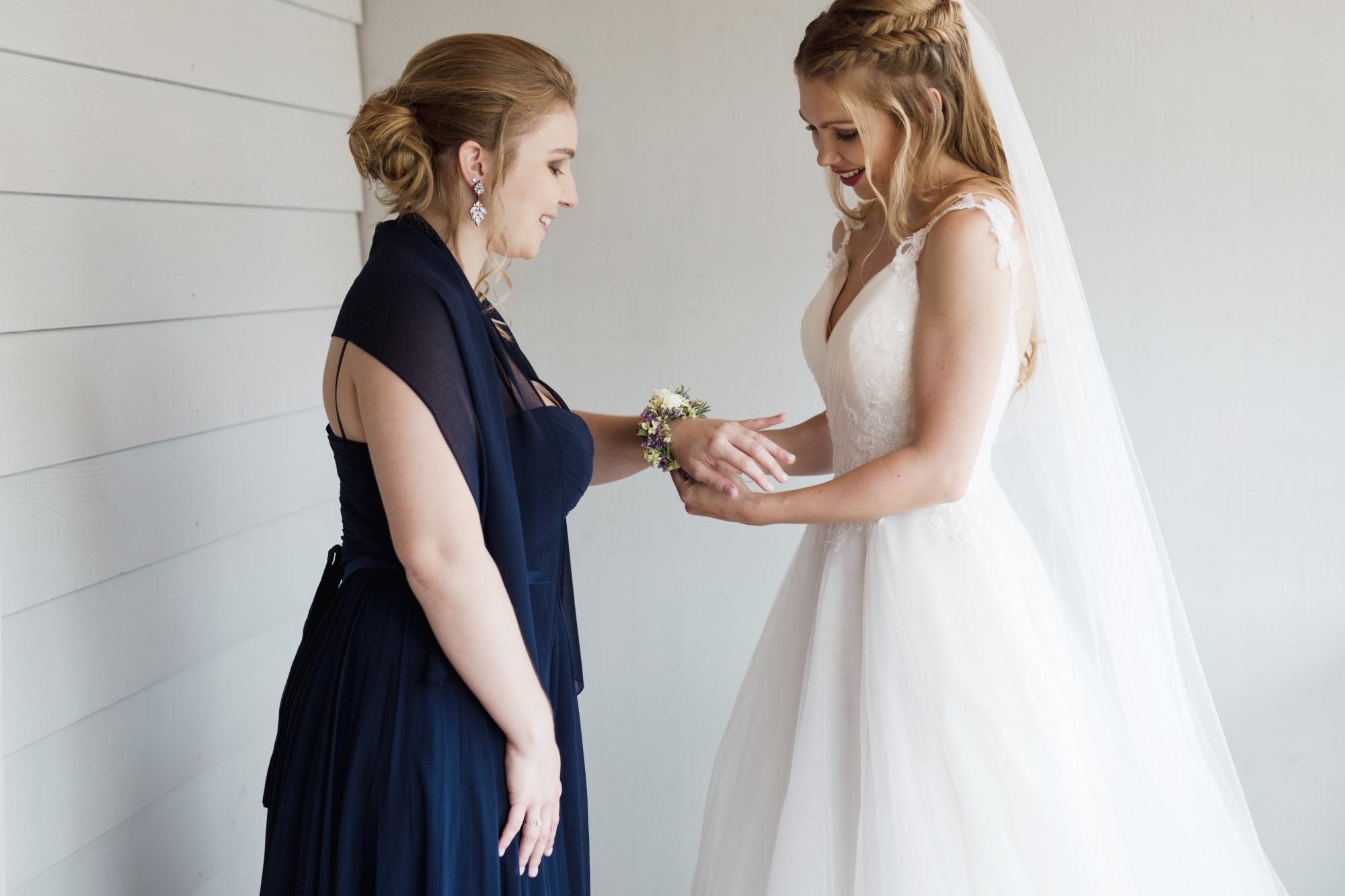 Die Braut zieht ihrer Schwester das Blumenarmband an