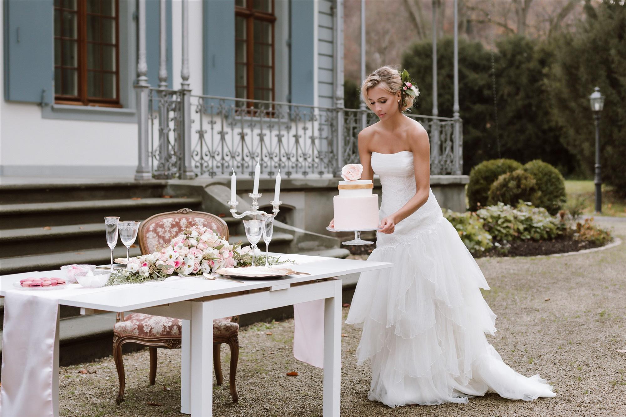 Die schöne Braut und wunderschöne Tischdekoration für die Hochzeit in Rosa, Weiss und Gold