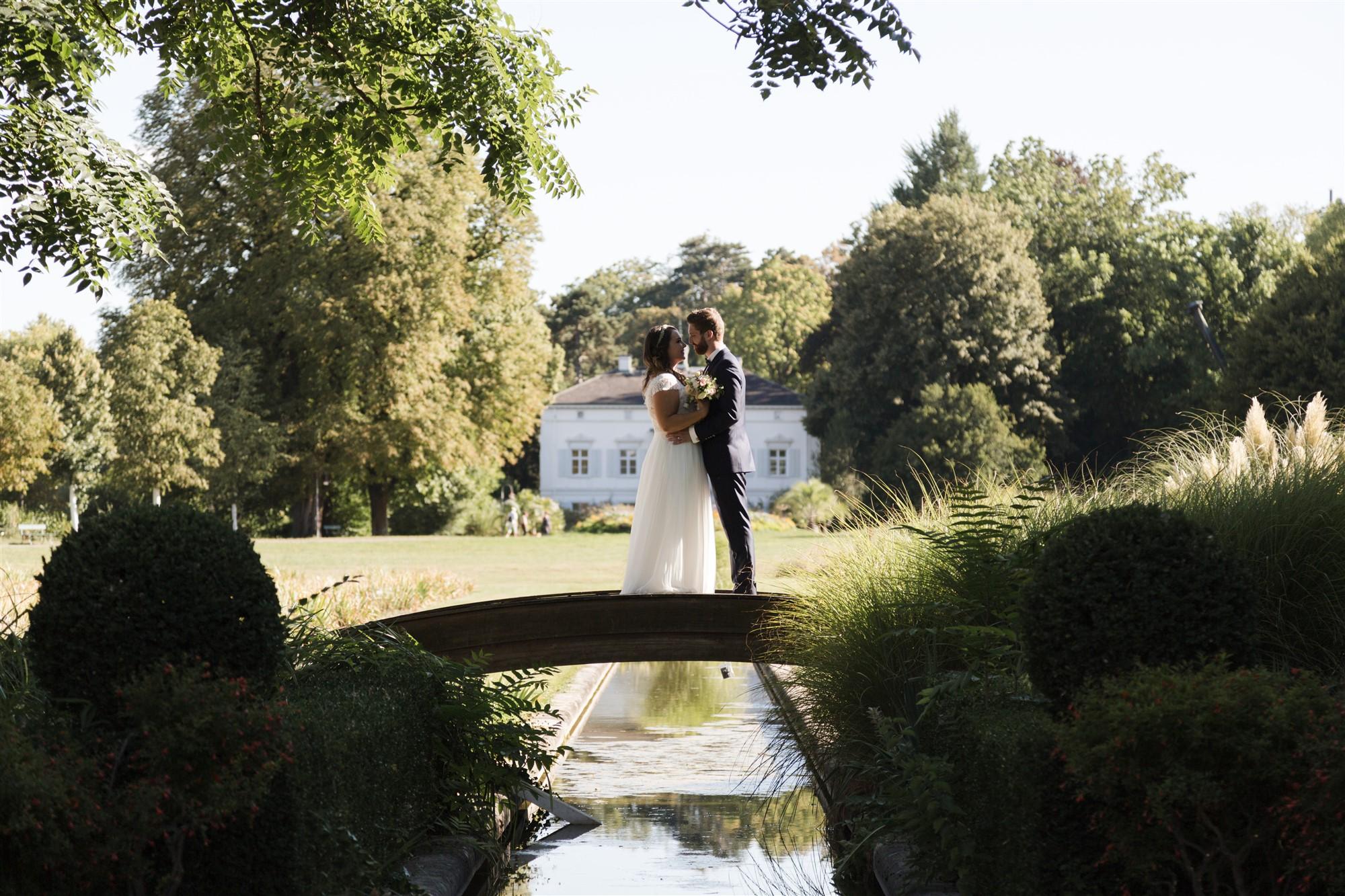 Das Brautpaar steht auf der Brücke in den Merian Gärten