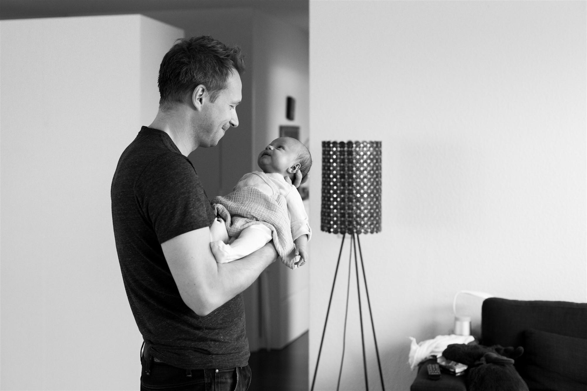 Newborn Homestory Fotoshooting - Der stolze Papa mit seinem Baby