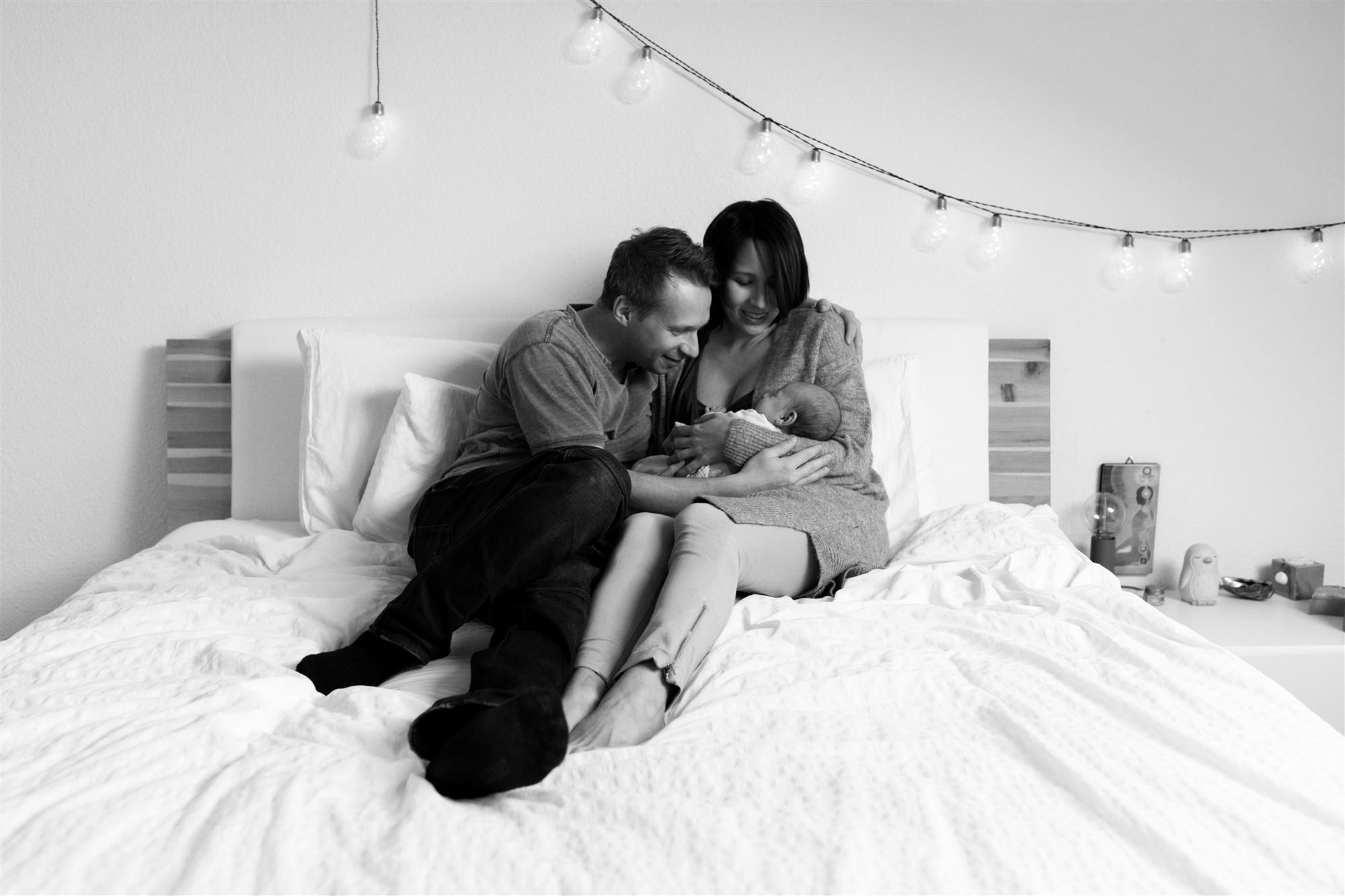 Newborn Homestory Fotoshooting - Die Eltern kuscheln mit ihrem Baby