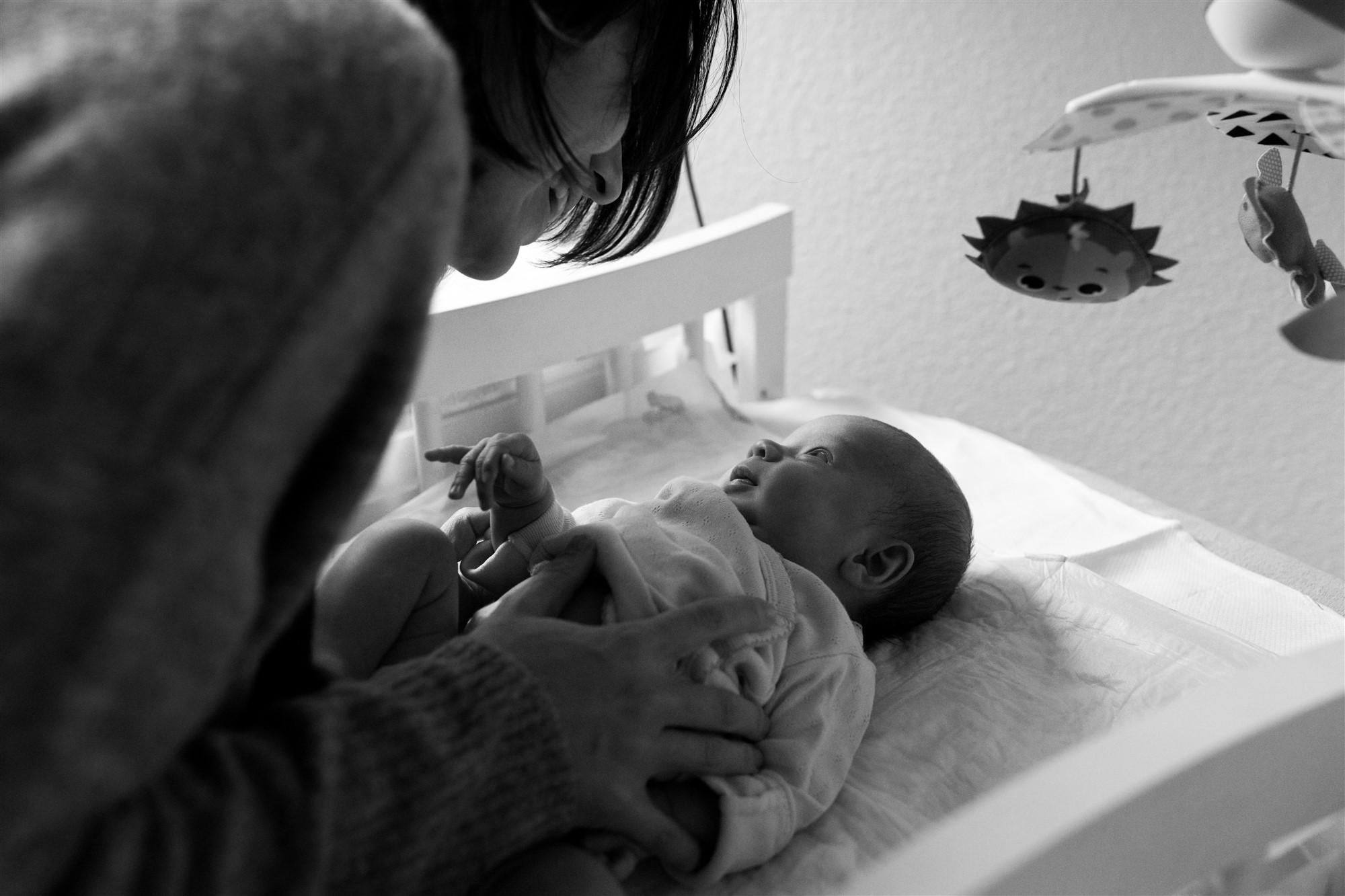 Newborn Homestory Fotoshooting - Die Mama wickelt ihr Baby