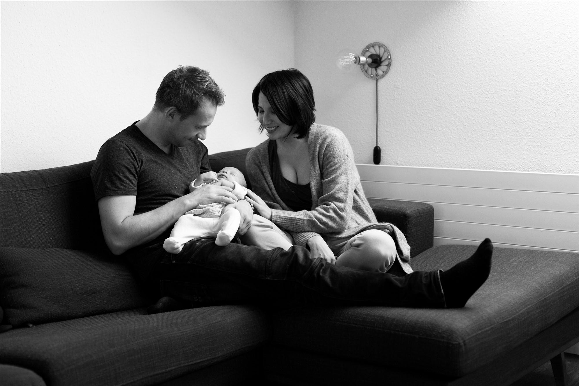 Newborn Homestory Fotoshooting - Die kleine Familie kuschelt auf dem Sofa