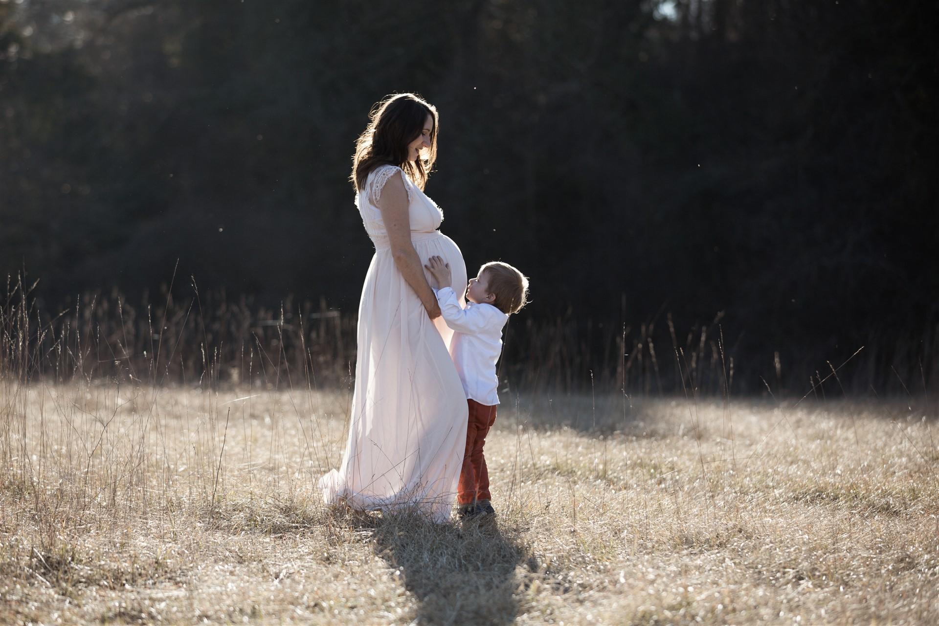 Babybauch Fotoshooting in der Natur mit der werdenden Mama und ihrem kleinen Sohn