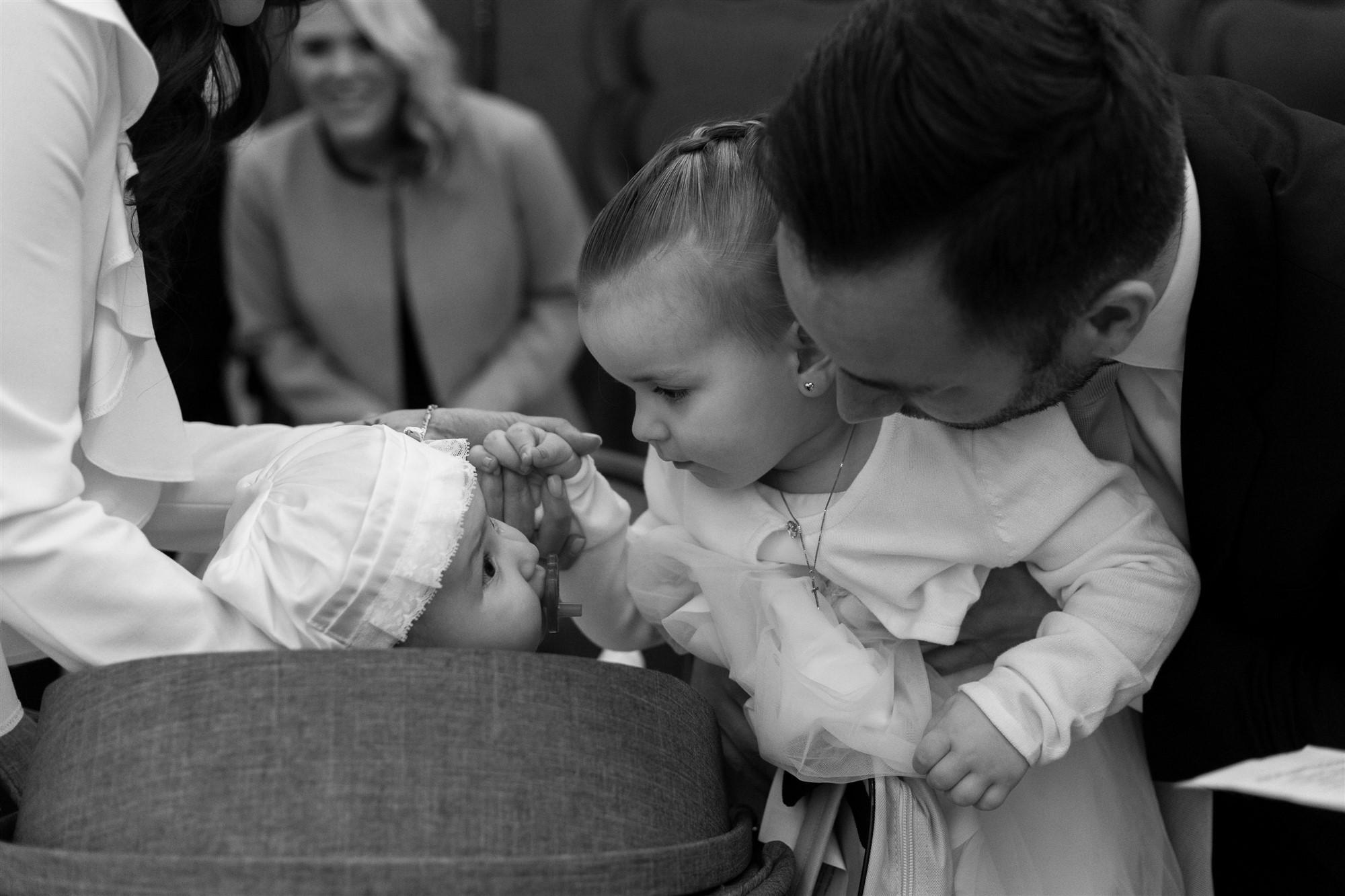 Die grosse Schwester segnet das Taufbaby