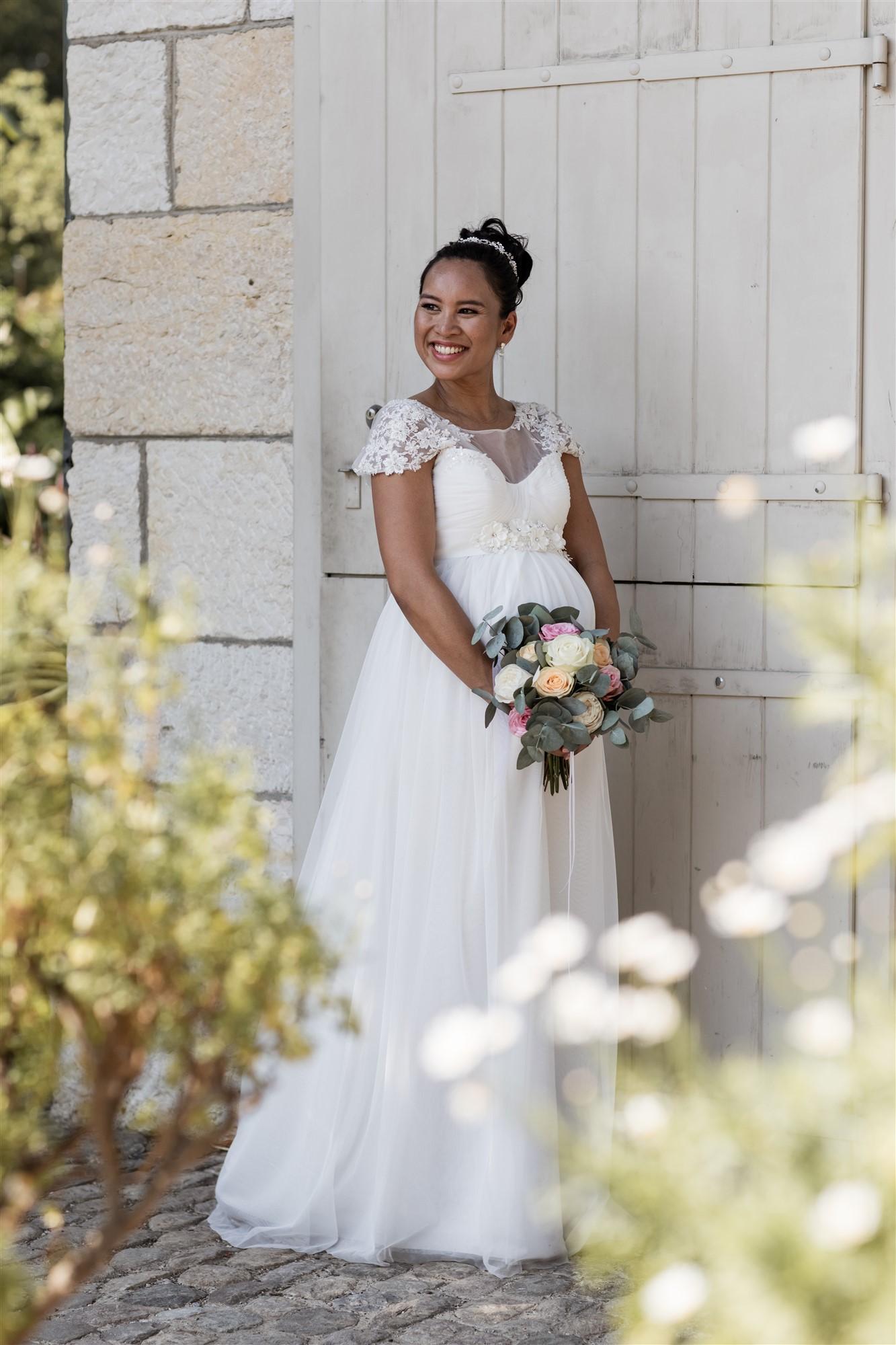 Die lachende Braut und ihr Babybauch beim romantischen Fotoshooting in den Merian Gärten