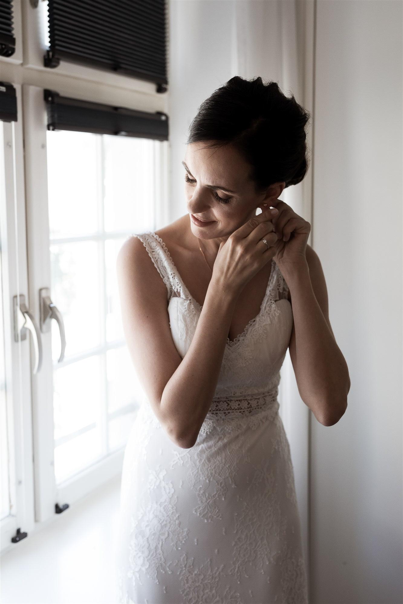 Getting Ready der Braut - Die Braut zieht ihre Ohrringe an - Hochzeit im Teufelhof Basel - Hochzeitsfotograf Nicole Kym