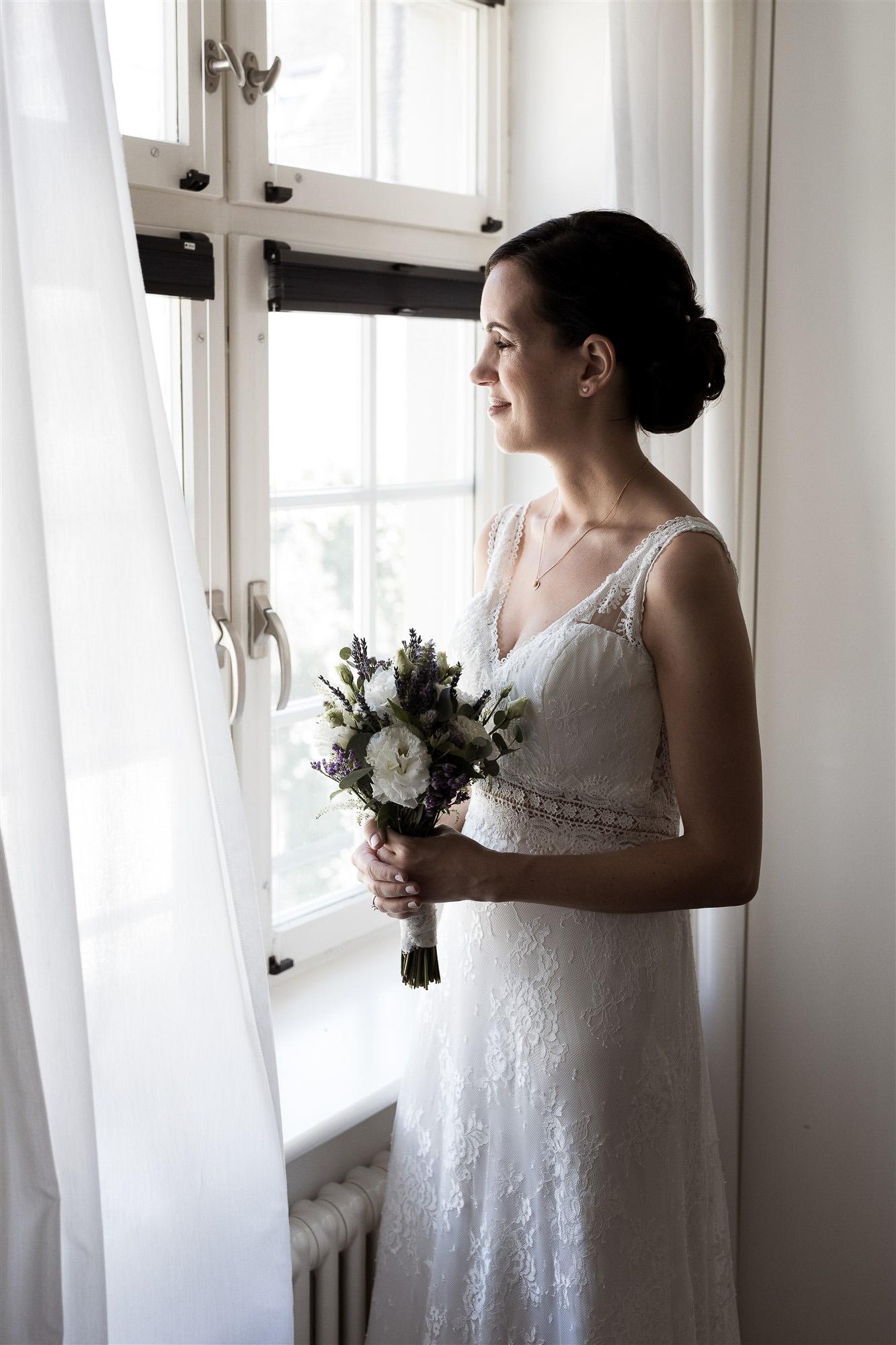 Getting Ready der Braut - Die Braut schaut gespannt aus dem Fenster - Hochzeit im Teufelhof Basel - Hochzeitsfotograf Nicole Kym