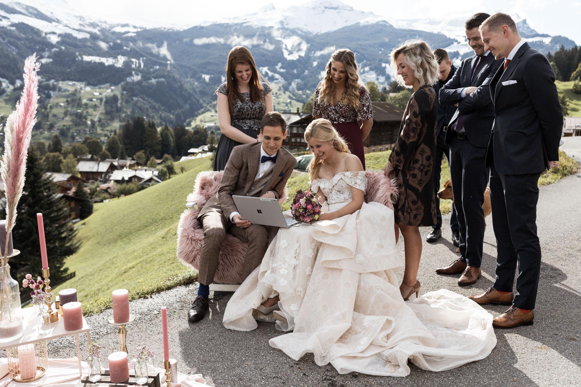 Das Brautpaar schaut sich die Glückwünsche der Familie am Laptop an - Hochzeit Grindelwald - Destination Wedding - Hochzeit in den Bergen - Freie Trauung - Hochzeitsfotograf