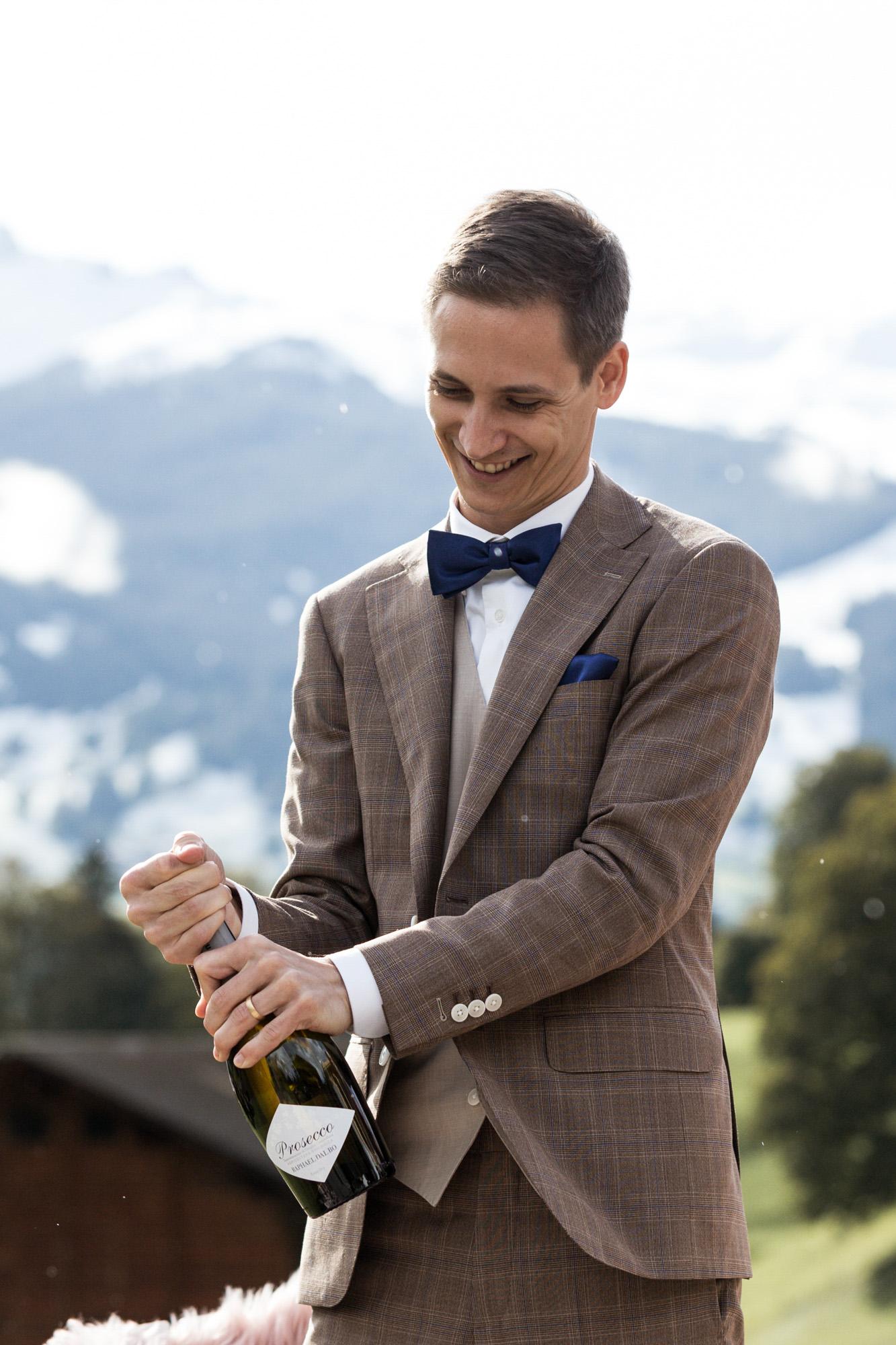 Der Bräutigam öffnet den Champagner - Hochzeit in Grindelwald - Hochzeitsfotograf Basel