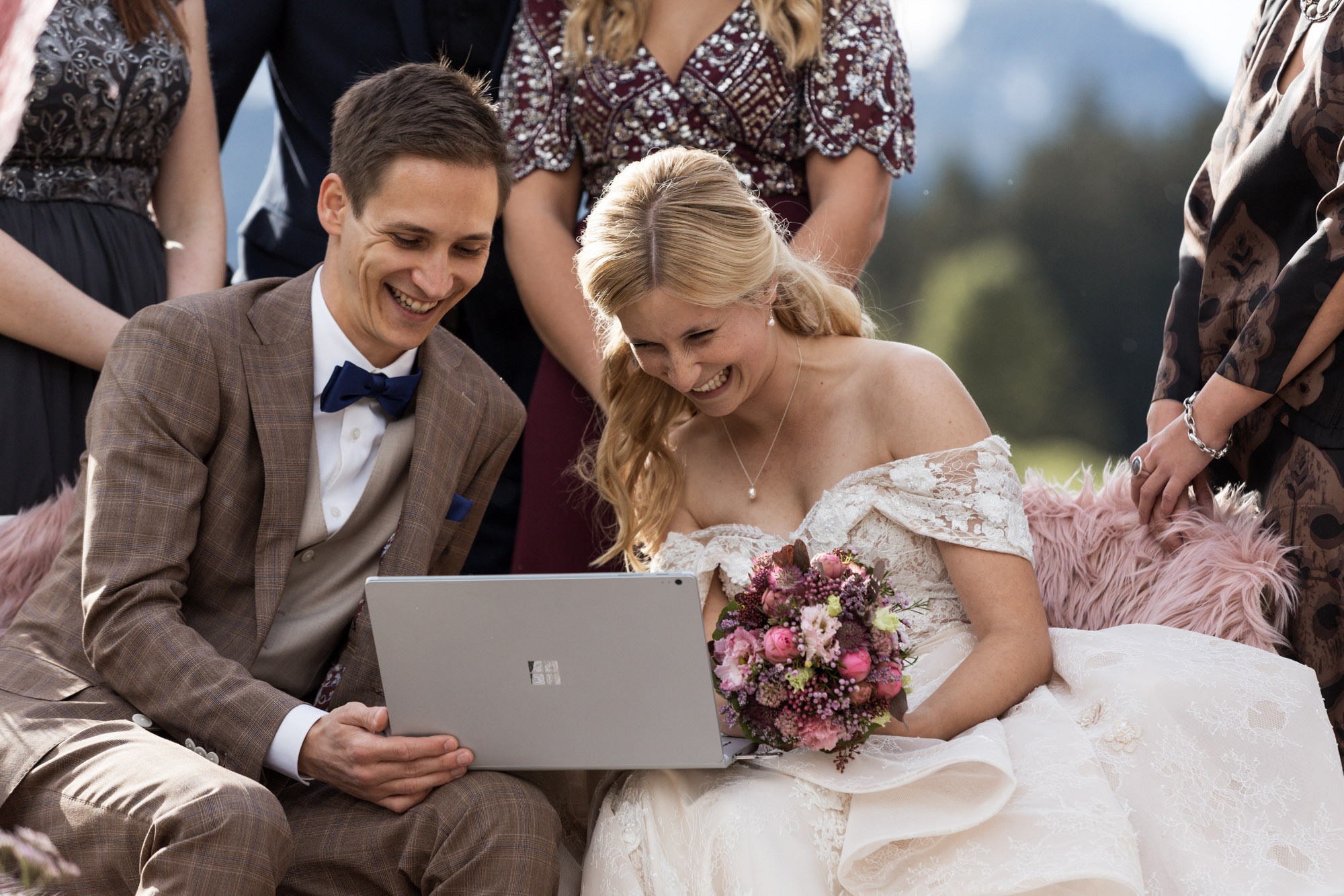 Das Brautpaar schaut sich die Glückwünsche der Familien auf dem Laptop an - Hochzeit in den Bergen - Freie Trauung - Hochzeitsfotograf