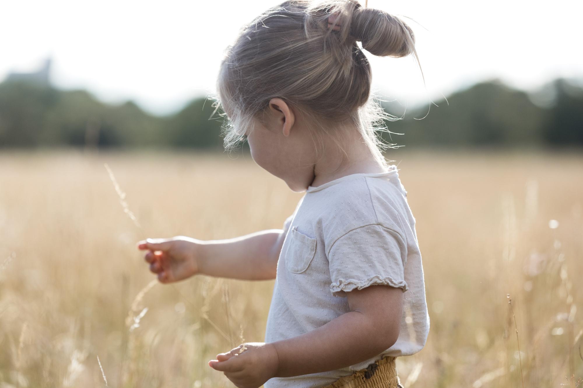 Familienfotoshooting - Das Mädchen spielt in der Natur - Familienreportage - ungestellte Familienbilder