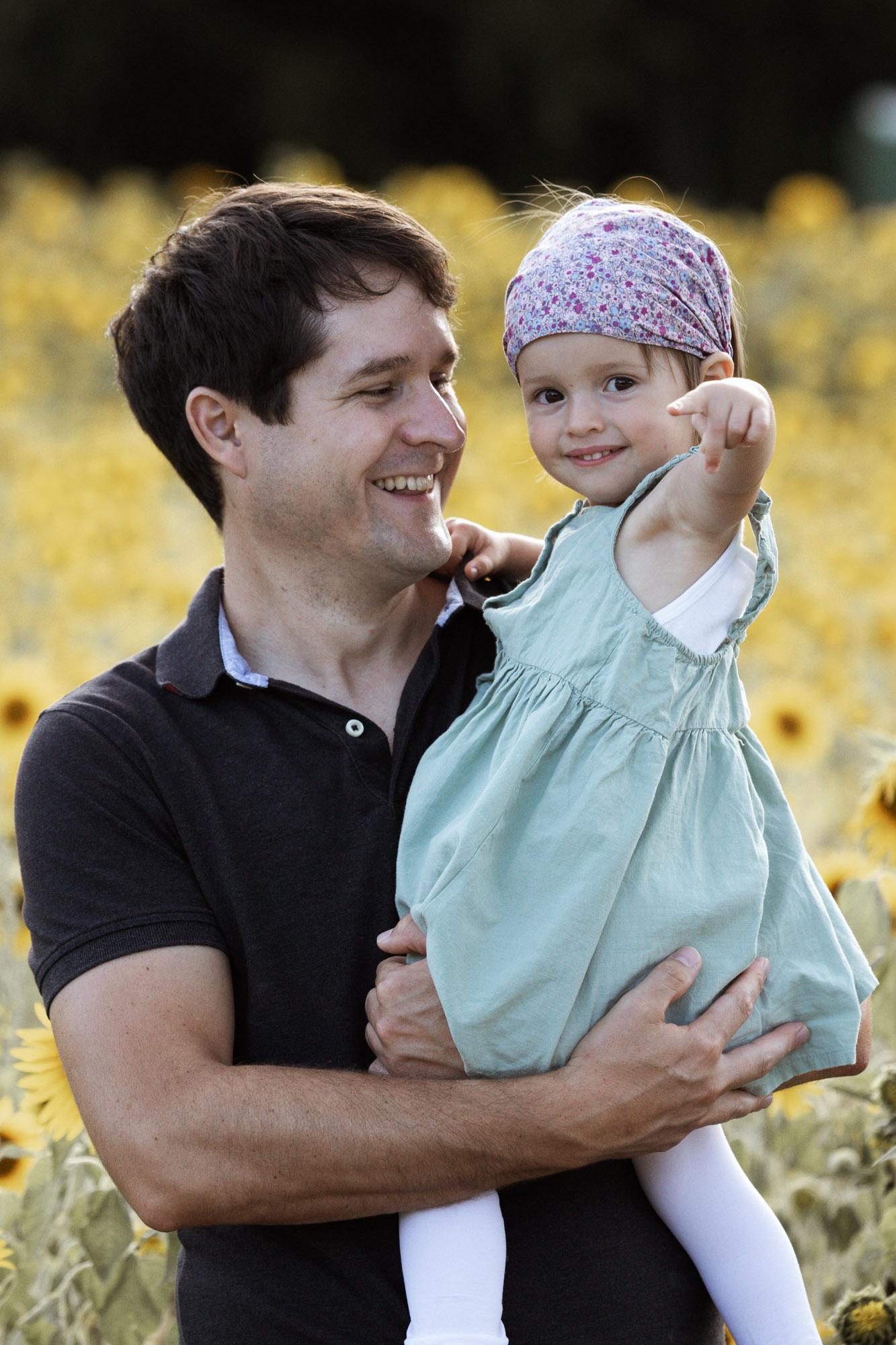 Babybauch und Familienfotoshooting in den Merian Gärten - Der Papa mit seiner süssen Tochter im Sonnenblumenfeld