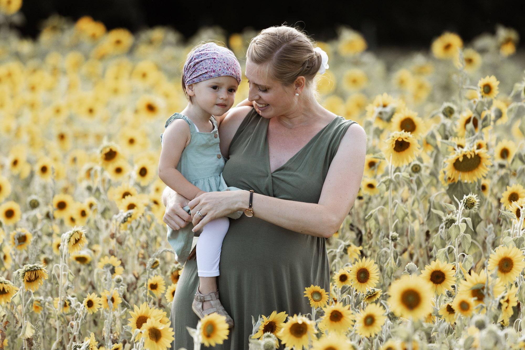 Babybauch und Familienfotoshooting in den Merian Gärten - Die Mama mit ihrer süssen Tochter im Sonnenblumenfeld