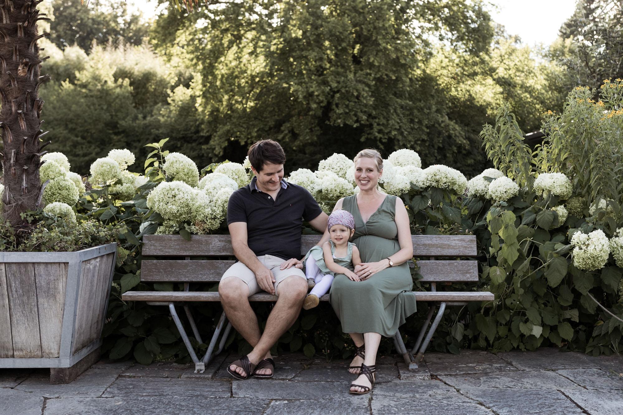 Babybauch und Familienfotoshooting in den Merian Gärten - Die Familie sitzt auf der Parkbank