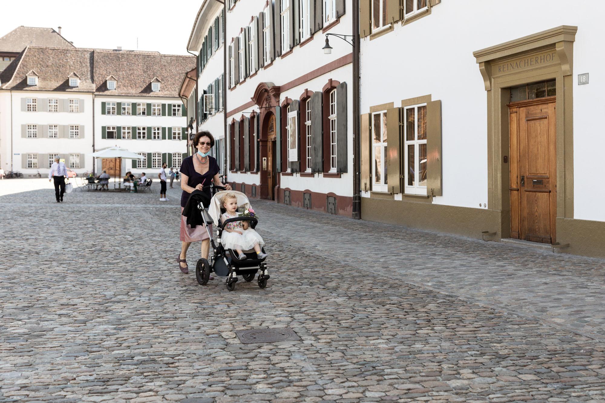 Die Oma bringt die süsse Tochter dem Brautpaar auf dem Münsterplatz - Hochzeitsfotografen Basel